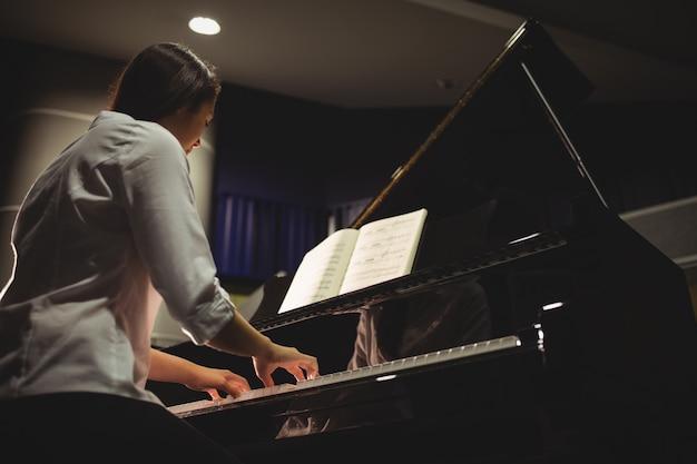 Studentka gra na pianinie