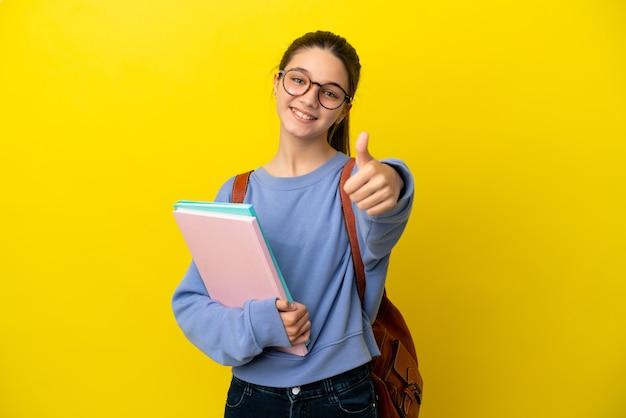 Studentka kobieta na żółtym tle z kciukami do góry, ponieważ wydarzyło się coś dobrego