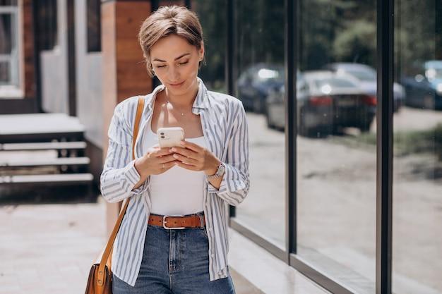 Studentka korzystająca z telefonu poza ulicą