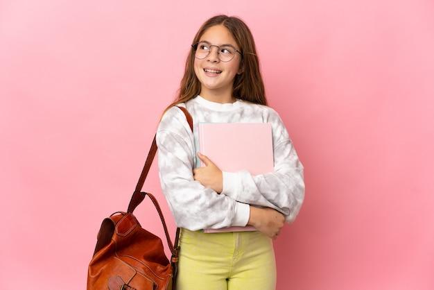 Studentka mała dziewczynka na białym tle różowej ścianie myślenia, patrząc w górę