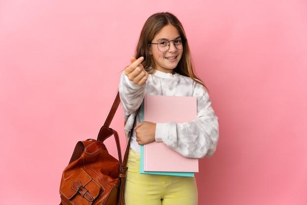 Studentka mała dziewczynka na izolowanym różowym tle zarabiania pieniędzy gest
