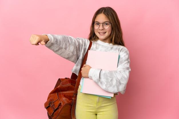 Studentka mała dziewczynka na różowym tle, pokazująca gest kciuka w górę