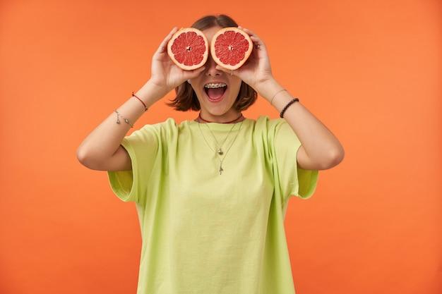 Studentka, młoda dama z krótkimi włosami brunetki, trzymając grejpfrut na oczach. zdziwiony wygląd. stojąc nad pomarańczową ścianą. nosi zielony t-shirt, aparat ortodontyczny i bransoletki