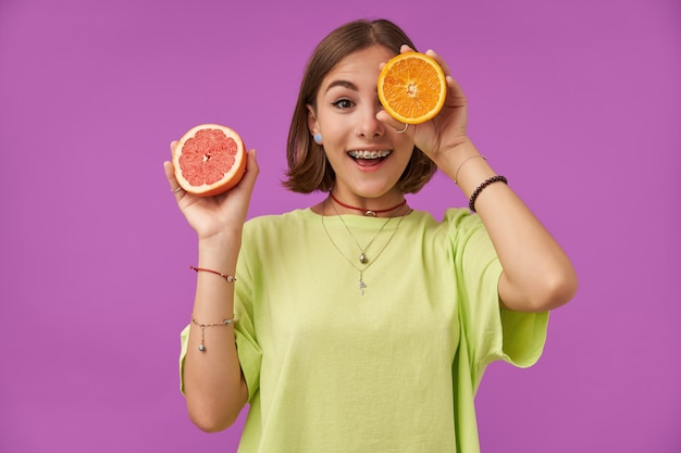 Studentka, młoda zdziwiona dama z krótkimi włosami brunetki. trzymając pomarańczę nad okiem, zasłoń jedno oko. stojąc nad fioletową ścianą. nosi zielony t-shirt, naszyjnik, szelki i bransoletki