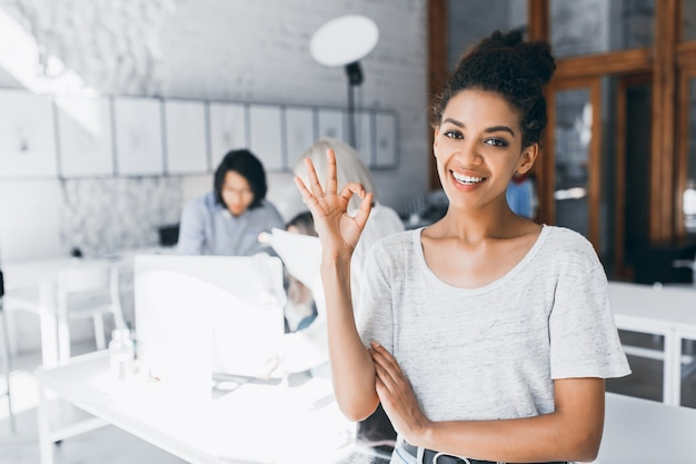 Studentka mulatu kręconego pozująca z uśmiechem i znakiem okej po trudnym teście na międzynarodowym uniwersytecie. kryty portret afrykańskiej kobiety pracy jako menedżer w biurze z młodym azjatyckim mężczyzną w tyle.
