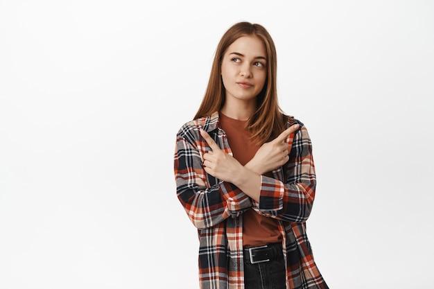 Studentka niezdecydowana myśląca, wskazująca na boki i na dwa sposoby, przygryzająca wargę w zamyśleniu, podejmuje decyzję, wybiera między wariantami, stoi przy białej ścianie