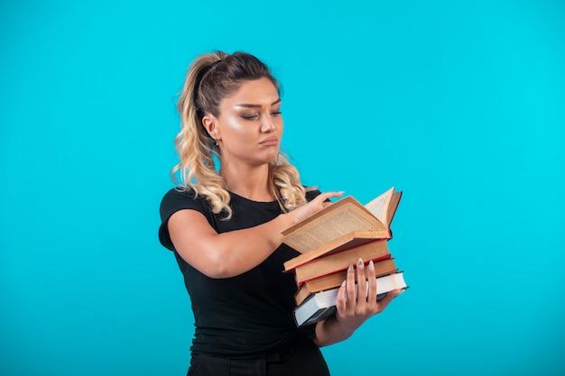 Studentka posiadająca duży zapas książek i czytania.
