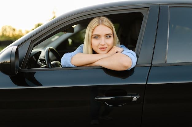 Studentka pozuje w samochodzie, lekcja w szkole nauki jazdy. mężczyzna uczy pani prowadzenia pojazdu.