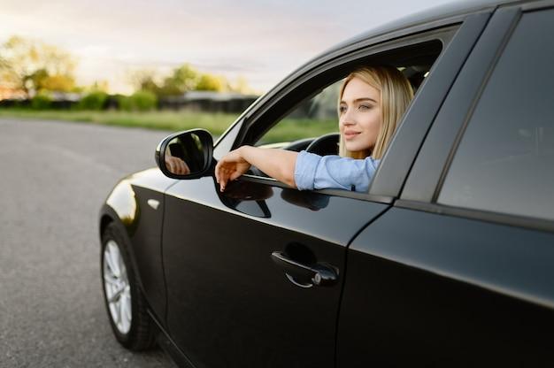 Studentka pozuje w samochodzie, szkoła jazdy