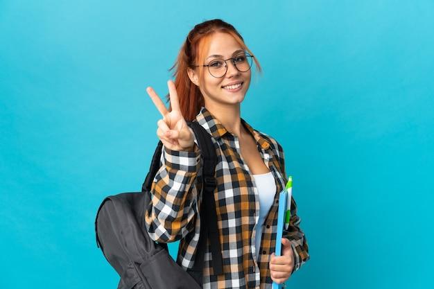 Studentka rosjanka na białym tle na niebiesko, uśmiechając się i pokazując znak zwycięstwa