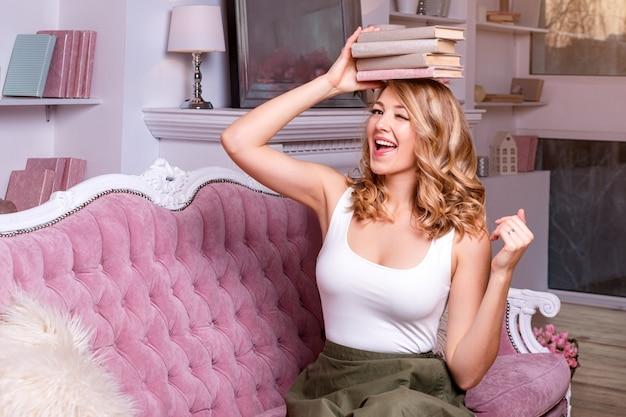 Studentka równoważenia książek na głowie i mrugania. piękna blondynka trzyma stos książek na głowie.