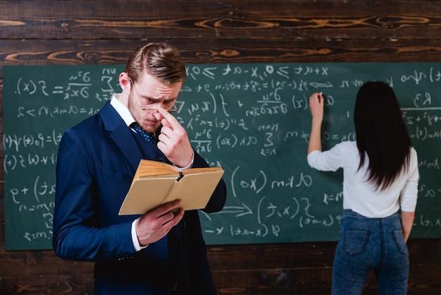 Studentka rozwiązująca równanie na tablicy młody nauczyciel z krótkim włosiem dopasowujący okulary podczas czytania boo