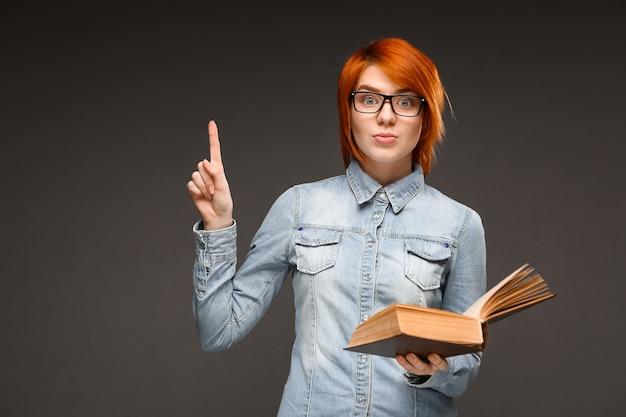 Studentka rudowłosa trzyma książkę, znalazła rozwiązanie