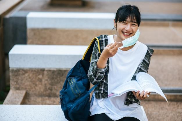 Studentka siedzi na schodach i poczyta książkę.
