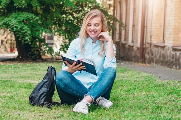 Studentka siedzi na trawie, czyta książkę i uśmiecha się w parku na tle uniwersytetu