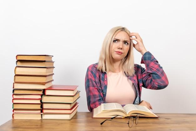 Studentka siedzi z książkami, czytanie i myślenie na białym tle