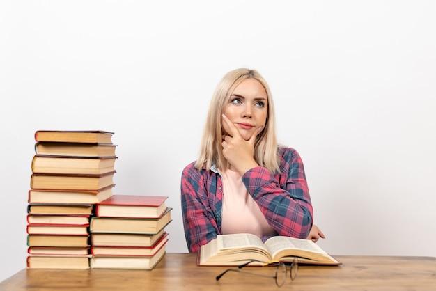 Studentka siedzi z książkami i myśli na białym tle