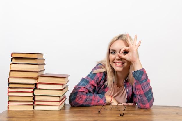 Studentka siedzi z różnymi książkami na białym tle