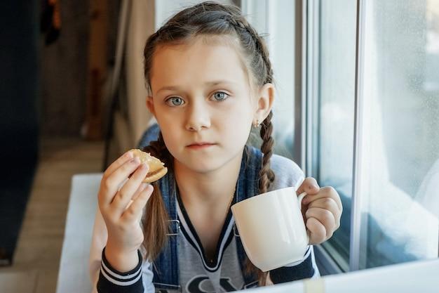 Studentka studiuje online z nauczycielem wideorozmów, szczęśliwa młoda dziewczyna słucha wykładu, ogląda na laptopie w domu i pije herbatę? jeść ciasteczka. koronawirus covid-19.