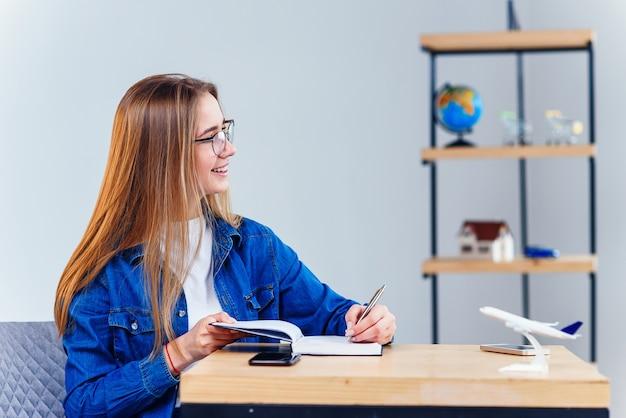 Studentka szuka okna i marzy o wakacjach podczas nauki w białym salonie. studiowanie geografii z globusem. urocza uczennica w dżinsowych ubraniach sprawia, że hometask.
