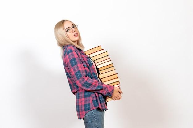 Studentka trzyma różne ciężkie książki na białym tle
