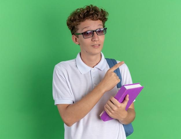 Studentka w swobodnym ubraniu, w okularach z plecakiem, trzymająca notatnik, patrząca w kamerę, szczęśliwa i pewna siebie, wskazując palcem wskazującym w bok