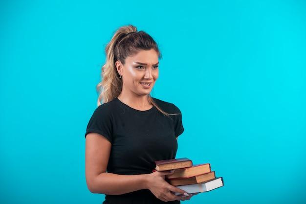 Studentka z dużym zapasem książek i czuje się zmęczona