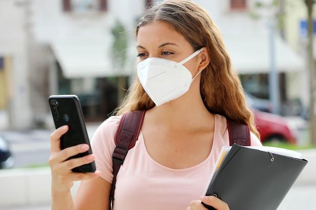 Studentka z maską ochronną, czytając wiadomość na smartfonie na ulicy