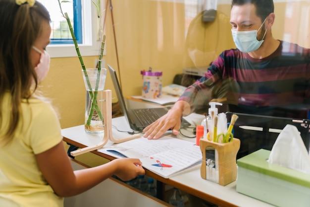 Studentka z maską oddająca pracę domową nauczycielowi przez ekran z metakrylanu