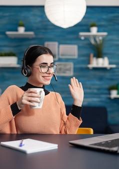 Studentka z okularami i filiżanką kawy w ręku pozdrawiając swojego nauczyciela podczas spotkania wideorozmów mówiących o stopniu uniwersyteckim. nastolatek ze słuchawkami na głowie siedzący przy biurku
