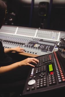 Studentka za pomocą klawiatury miksera dźwięku