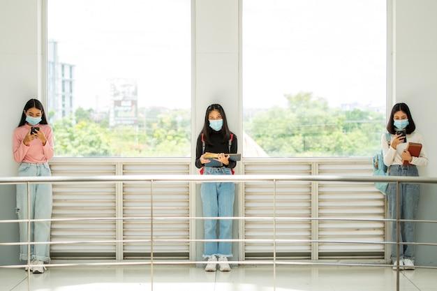 Studentki uniwersytetu siedzą w odstępach w klasie dystansowania społecznego, aby zapobiegać chorobom zakaźnym.