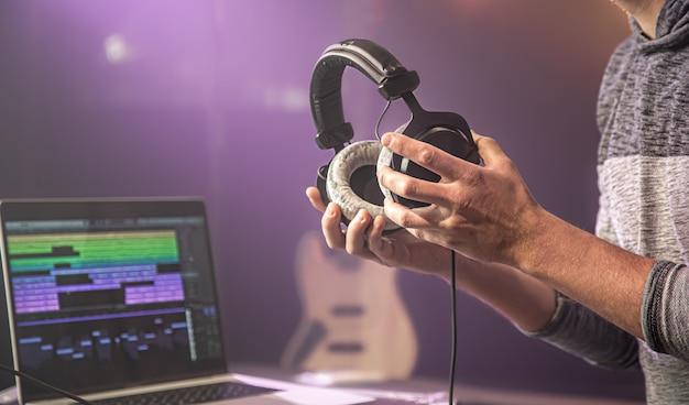 Studio audio słuchawki do nagrywania dźwięku w męskich rękach na niewyraźnej przestrzeni studia muzycznego z monitorem laptopa z bliska.