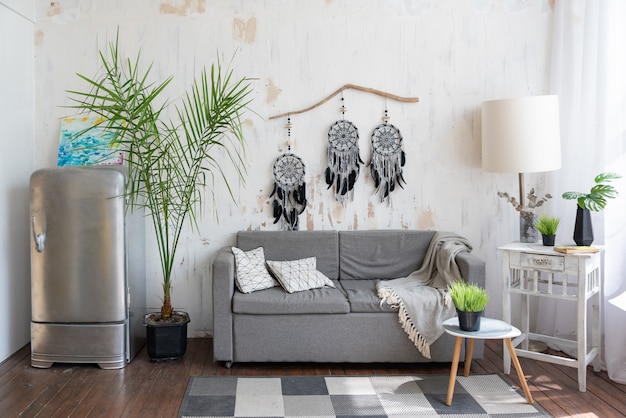 Studio do salonu z szarą sofą i łapaczem snów