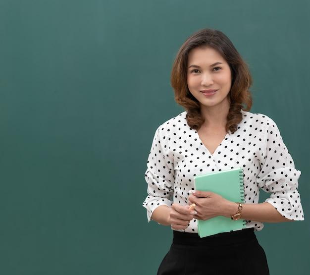 Studio flash light shot, piękna azjatycka kobieta trzyma książkę i kredę stojąc przed czarną tablicą z miejsca na kopię.