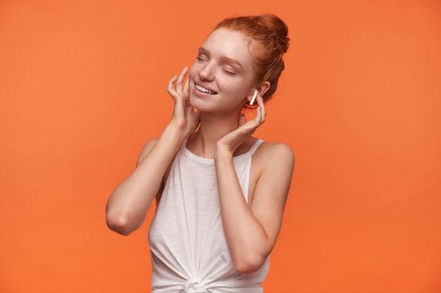 Studio fotograficzne dobrze wyglądającej młodej kobiety z czerwonymi włosami związanymi w węzeł, pozującej na pomarańczowym tle z podniesionymi rękami do uszu, słuchającej utworu muzycznego z zamkniętymi oczami, noszącej biały top