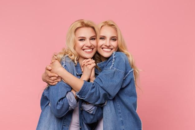 Studio fotograficzne młodych uradowanych, uroczych sióstr blondynki z długimi falującymi włosami, patrząc w kamerę z czarującymi uśmiechami, obejmując się czule, stojąc na różowym tle