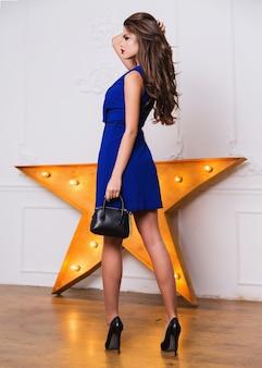 Studio fotograficzne modelki o pięknej twarzy i idealnym ciele. dekolt na krótkiej niebieskiej sukience, otwarte ramiona