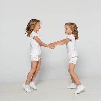 Studio fotograficzne przedstawiające dwie figlarne bliźniaczki