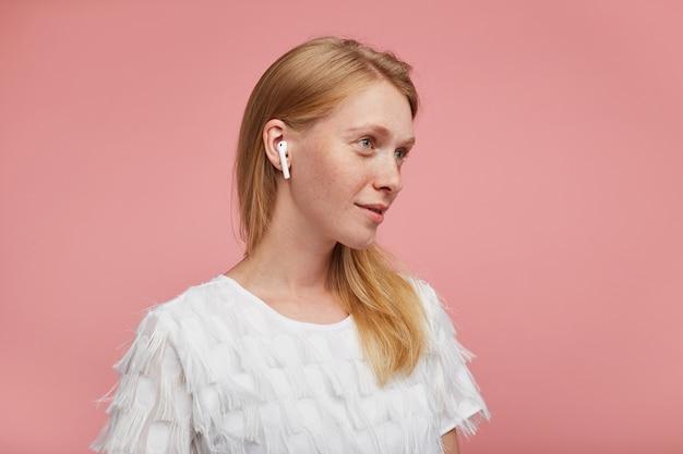 Studio fotograficzne uroczej młodej pozytywnej rudowłosej pani ubranej w eleganckie ubrania, pozując na różowym tle ze słuchawkami, patrząc przed siebie i uśmiechając się delikatnie
