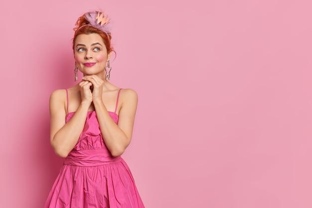 Studio fotograficzne z zamyślonym, marzycielskim wyrazem twarzy ma jasny makijaż, trzyma dłonie pod brodą, przygotowuje się do przyjęcia karnawałowego, nosi koronę, a różowa sukienka stoi w pomieszczeniu z pustym miejscem na promocję.