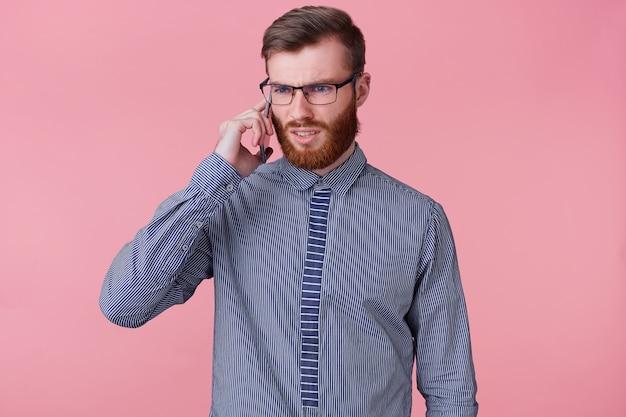 Studio fotograficzne zagubionego młodego brodatego mężczyzny w okularach, ubranego w pasiastą koszulę, któremu telefon mówi coś nieprzyjemnego. pojedynczo na różowym tle.
