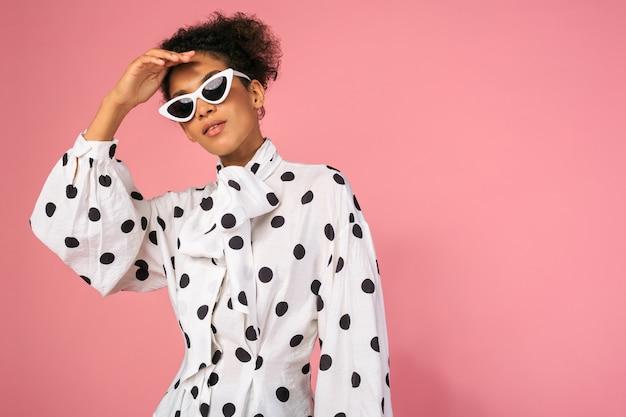 Studio fotografii afrykańskiej czarnej kobiety w stylowej sukience i białych okularach przeciwsłonecznych
