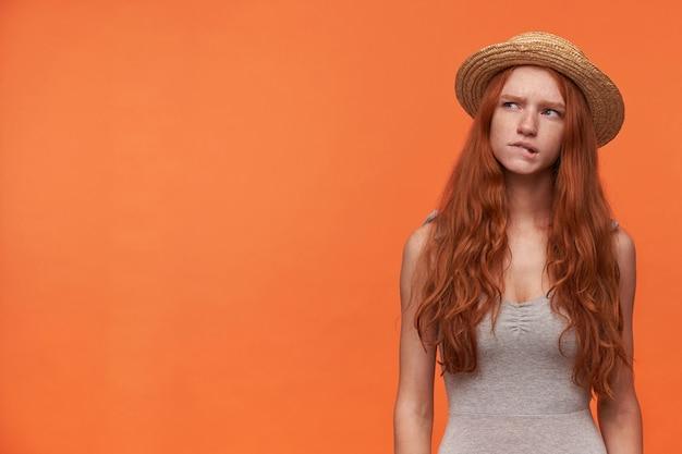 Studio fotografii ładnej młodej rudowłosej kobiety w zwykłym ubraniu stojącej na pomarańczowym backgroung, w szarej koszuli i czapce, patrząc w zamyśleniu na bok i gryząc dolną wargę