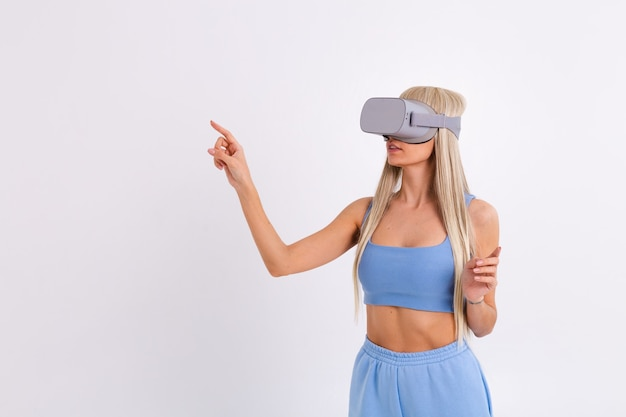 Studio fotografii młodej atrakcyjnej kobiety w ciepłym niebieskim modnym garniturze w okularach wirtualnej rzeczywistości na białym