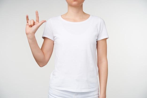 Studio fotografii młodej kobiety, trzymając rękę uniesioną do góry i tworząc gest podczas używania języka migowego, stojąc na białym tle w casual