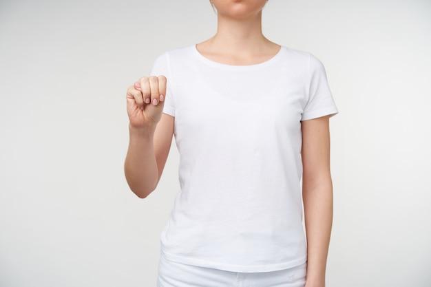 Studio fotografii młodej kobiety ubranej w białą koszulkę ściskając jej podniesioną rękę podczas formowania litery m na język migowy, odizolowane na białym tle