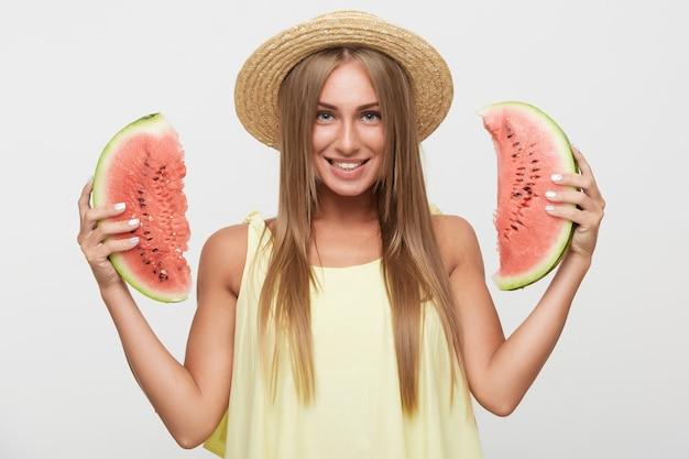 Studio fotografii młodej pięknej, długowłosej blondynki pani patrzy radośnie na aparat z szerokim uśmiechem, trzymając plasterki arbuza w uniesionych rękach, pozując na białym tle