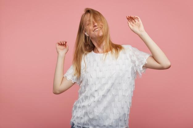 Studio fotografii młodej zadowolonej rudowłosej kobiety machającej swoimi lśniącymi włosami podczas tańca z uniesionymi rękami, uśmiechającej się wesoło, pozując na różowym tle
