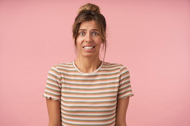 Studio fotografii młodej zielonookiej brunetki pokazującej zęby podczas wykrzywiania twarzy zmieszanej, odizolowanej na różowym tle z opuszczonymi rękami